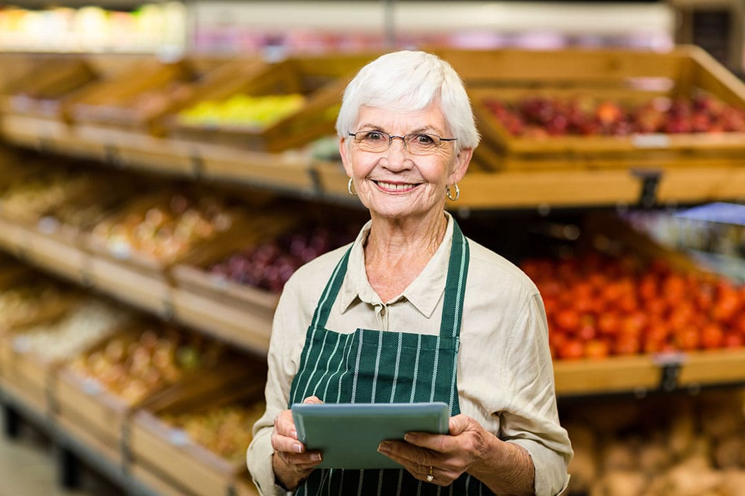 Older grocery store manager holding iPad